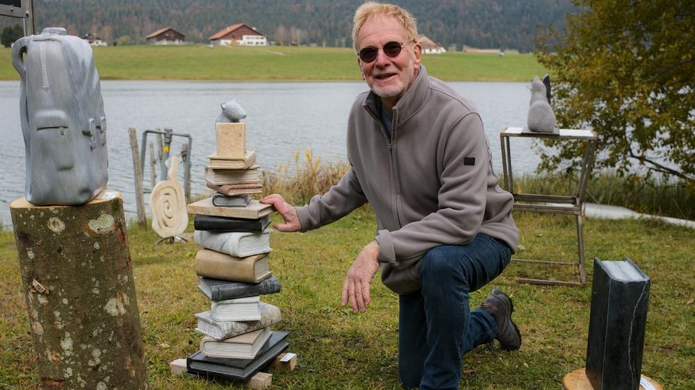 """Laurent Martin, au bord du lac des Taillères, à La Brévine, à côté de son """"Rat de bibliothèque"""". En pierres diverses, la pièce pèse 78 kilos et mesure 93 cm de haut."""