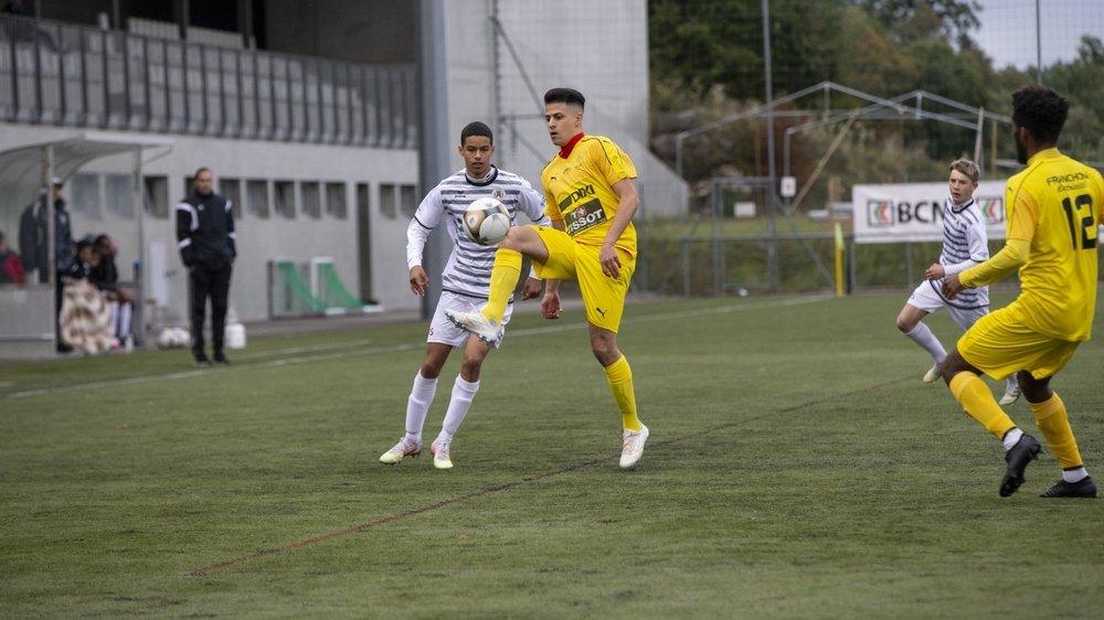 L'Audaxien Sami Boni (en blanc) à la lutte pour le ballon avec le Loclois Luca Leonti.