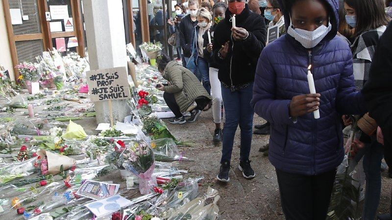 Des dizaines d'élèves et de parents ont déposé une rose blanche au pied des grilles du collège du Bois d'Aulne à Conflans-Sainte-Honorine.