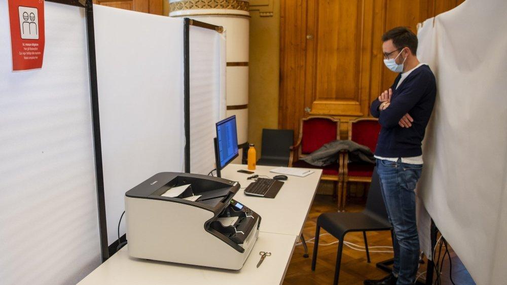 Un scrutateur scanne des bulletins de vote lors des élections communales ce dimanche 25 octobre à Neuchâtel.