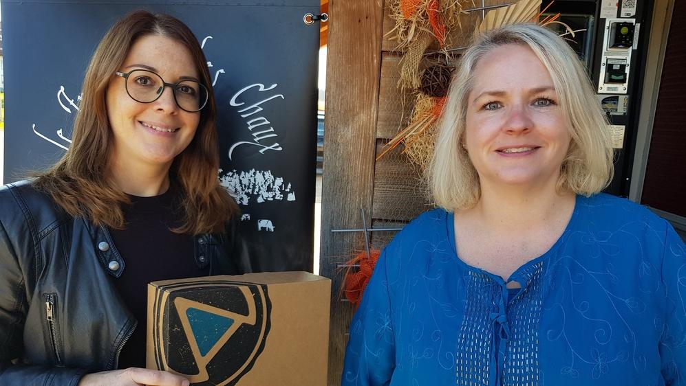 """Les fondatrices de L'Atelier du fromage Johana Eidam Vautherot (à gauche) et Lhney Steiner posent avec leur """"box"""" devant la fromagerie des Chaux, à La Chaux-du-Milieu."""