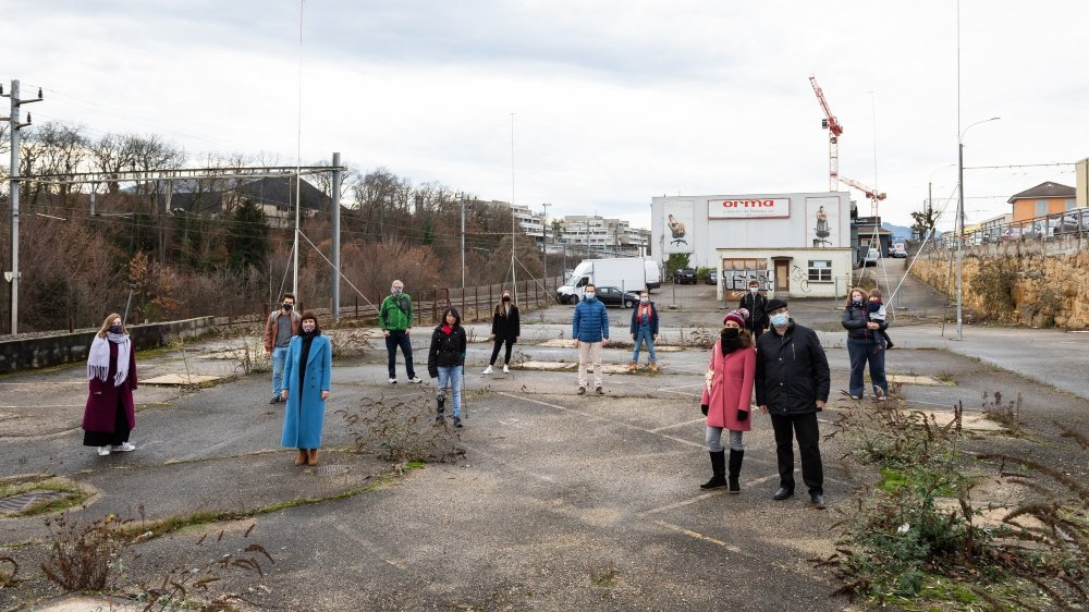 Yves Senn (devant, tout à droite, au côté de sa femme Maïté) et des membres de L'Avant-Scène opéra posent sur la parcelle où sera construit le centre d'art et de formation. A gauche la ligne de train. A droite, au-dessus, l'avenue des Portes-Rouges.