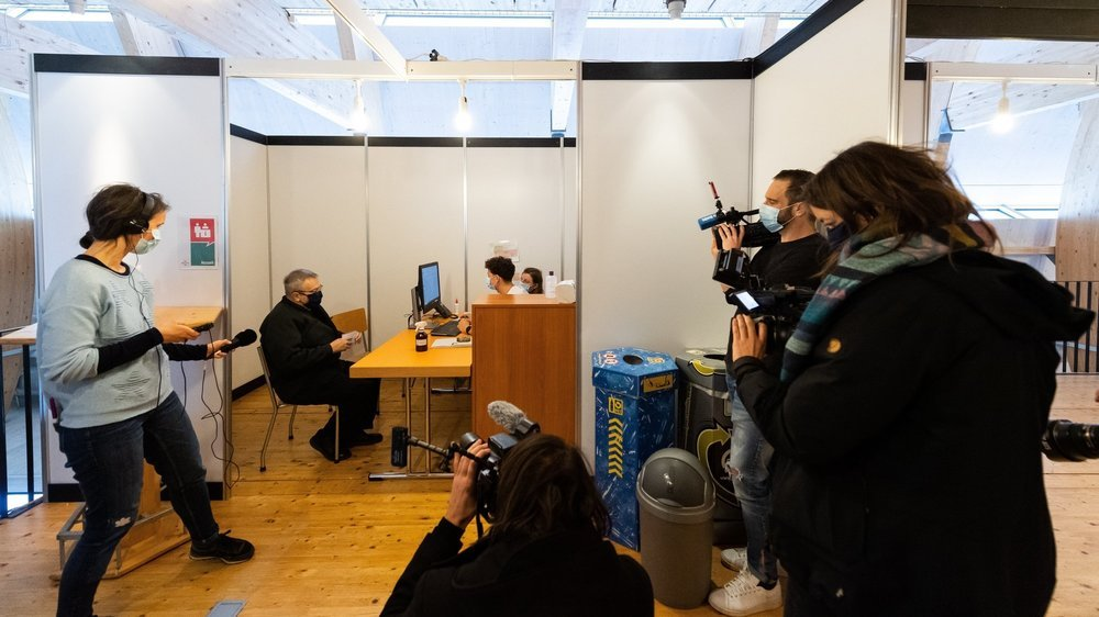 Des membres de l'équipe de Festi'neuch (au fond à droite) s'occupent notamment de l'accueil des patients qui viennent se faire vacciner contre le Covid-19, à Cernier. Photo prise le jour du lancement de la campagne cantonale de vaccination.