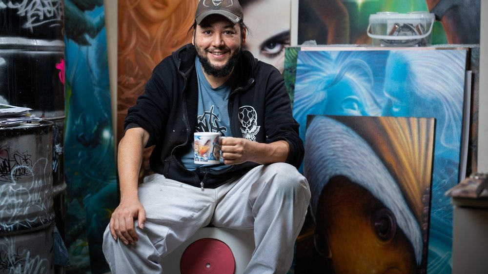 Le graffeur Soy, une tasse de thé dans la main, dans son atelier de La Chaux-de-Fonds.