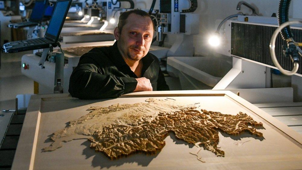 L'ingénieur Eric Marguet et une carte de la Suisse dont le relief a nécessité 240 heures de fraisage, soit 10 jours.
