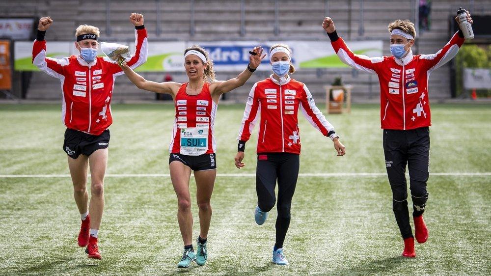 Elena Roos, la dernière relayeuse helvétique (deuxième depuis la gauche), est accompagnée vers l'arrivée par Joey Hadorn, Simona Aebersold et Matthias Kyburz (gauche à droite). L'équipe de Suisse a eu le temps de célébrer sa médaille d'or.