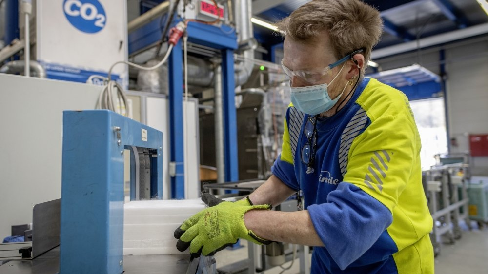 Un ouvrier de PanGas qui produit un bloc de glace carbonique.