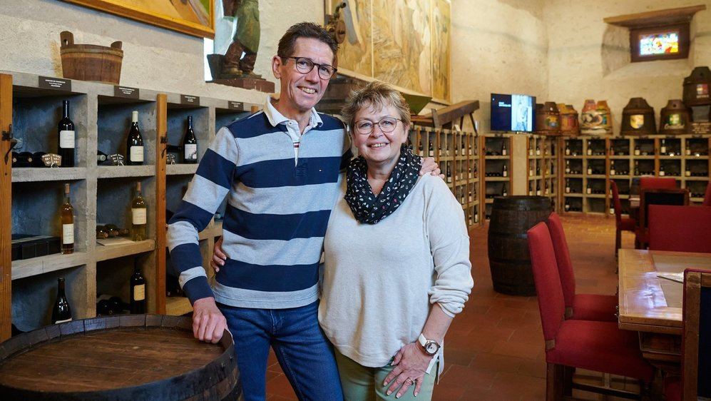 Pierre-Alain et Marianne Rohrer posent devant le cellier de l'œnothèque, dont les bouteilles sont désormais visibles.