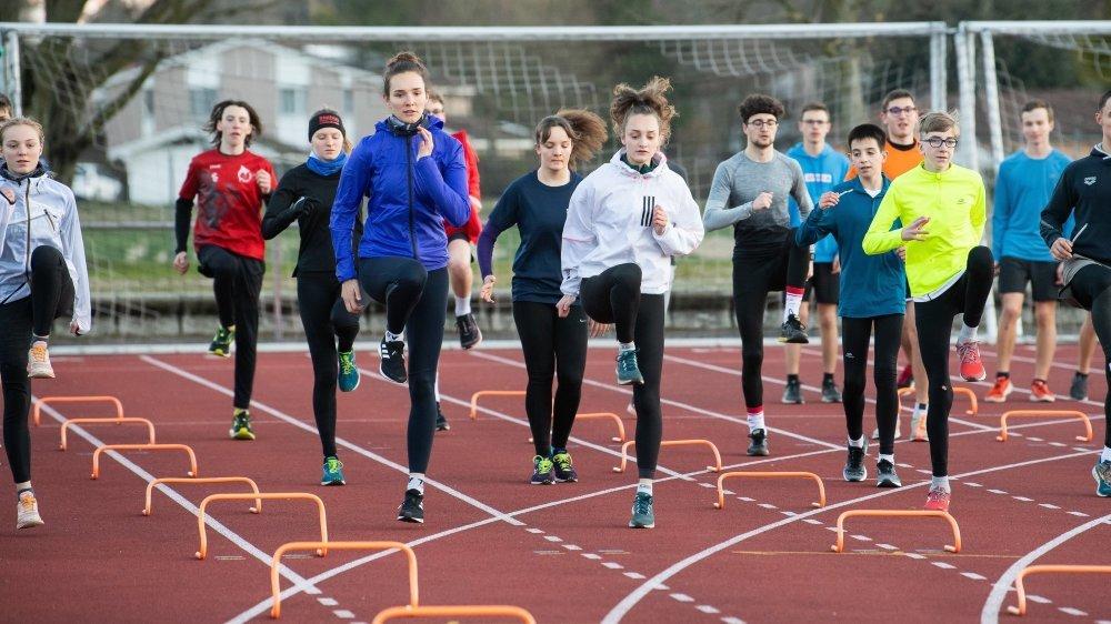 Coralie Gibson (à gauche en bleu) et Emilie Gibson (à droite en blanc) s'entraînent avec un groupe d'athlètes au stade du Littoral à Colombier.