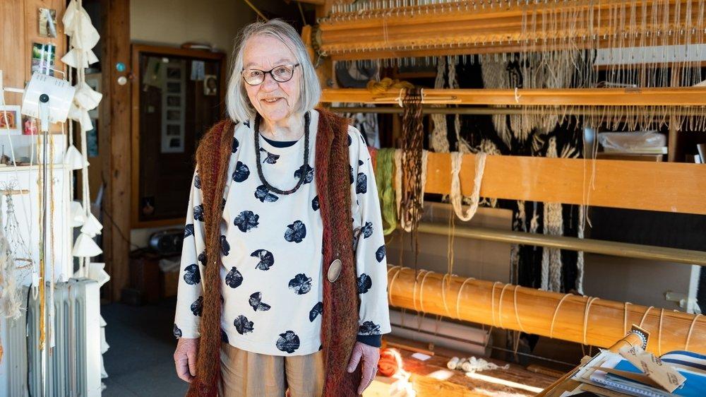 Jeanne-Odette devant son métier à tisser, outil de ses créations intemporelles et toujours modernes.