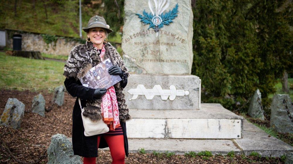 Dominique Wacker-Cao avec son livre devant le monument des Bourbakis à Neuchâtel, à l'emplacement de l'ancien cimetière du Mail.