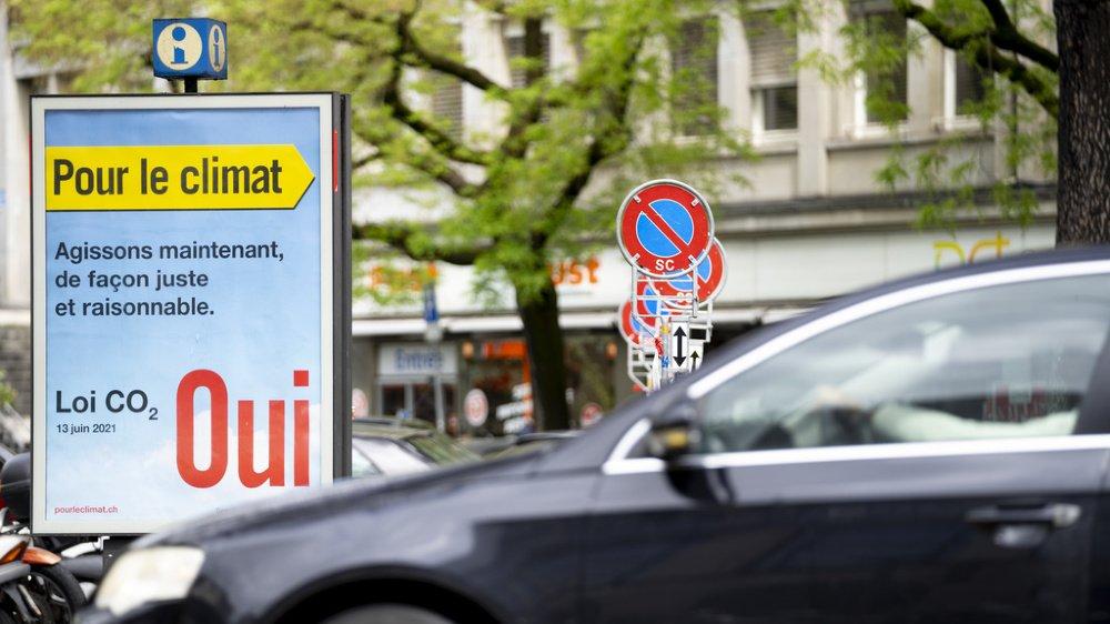 Une voiture passe devant une affiche invitant à voter oui à la loi sur le CO2.