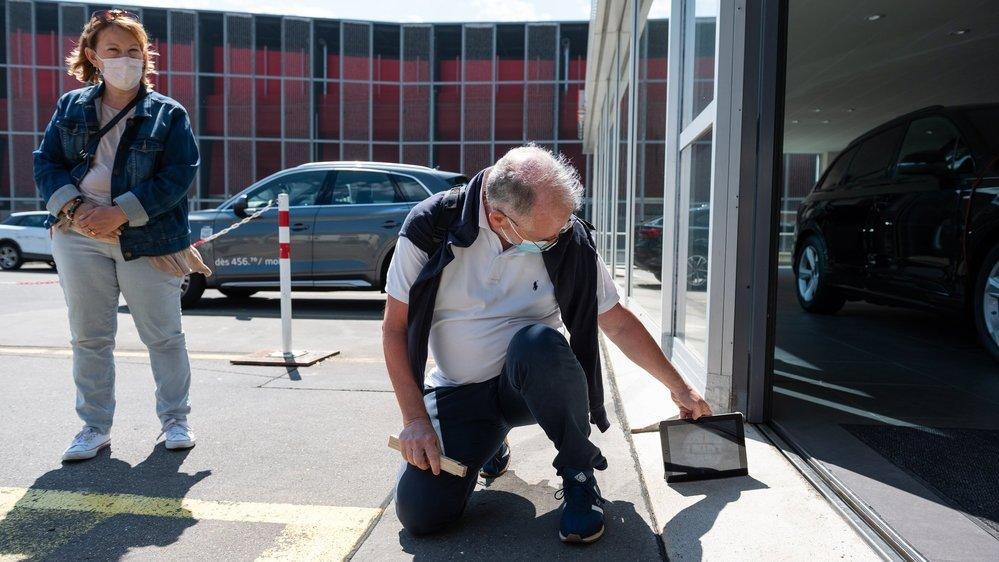 Une équipe de Pro Infirmis collecte des données sur l'accessibilité des bâtiments. Ici, à l'entrée du garage Senn, à Neuchâtel, on mesure la pente.  Neuchatel, le 29 mai 2021 Photo: Lucas Vuitel