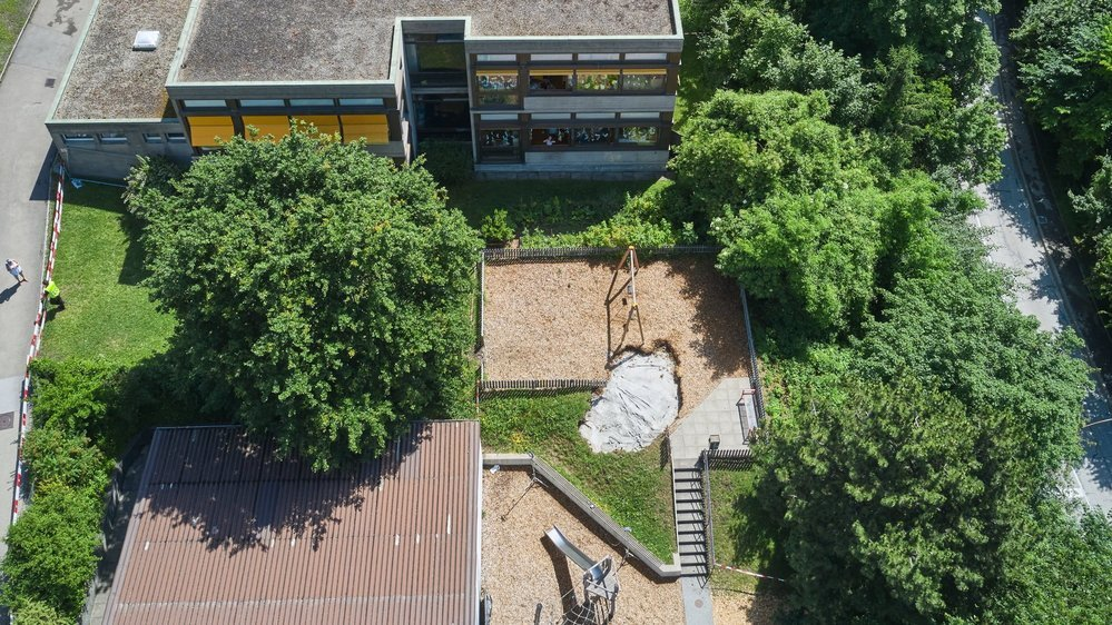 Le trou consécutif à l'écroulement de terrain à l'école des Charmettes a été bouché ce week-end avec du béton (tâche claire au bord de la place de jeux).