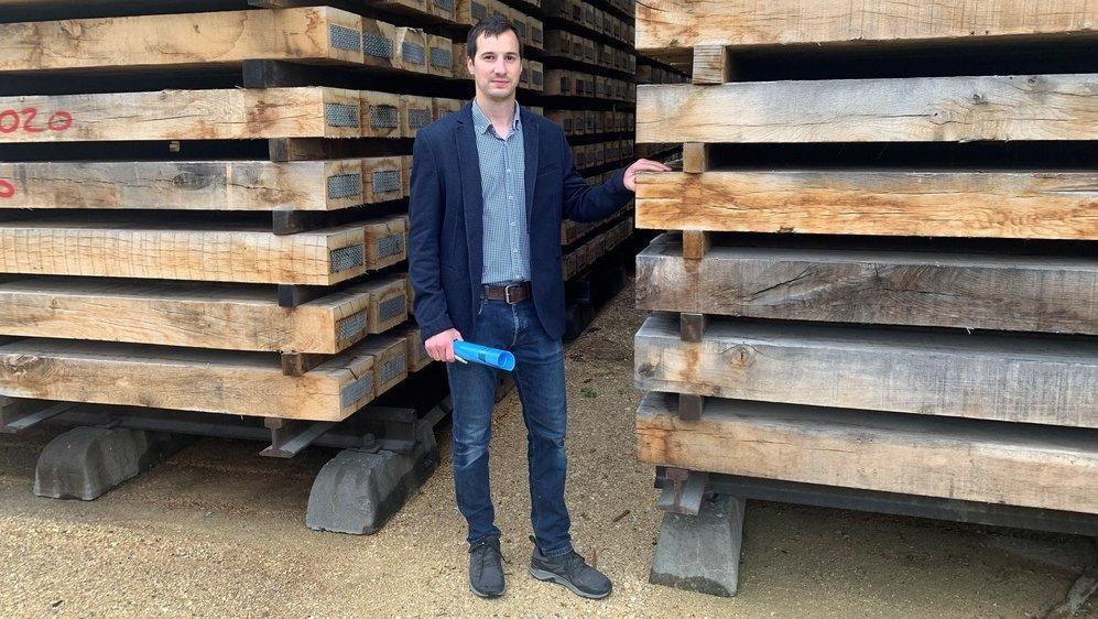 Benjamin Corbat, un des quatre patrons de l'entreprise familale Groupe Corbat, avec des traverses de chemin de fer sur le site de la future installation de production d'hydrogène à Glovelier.