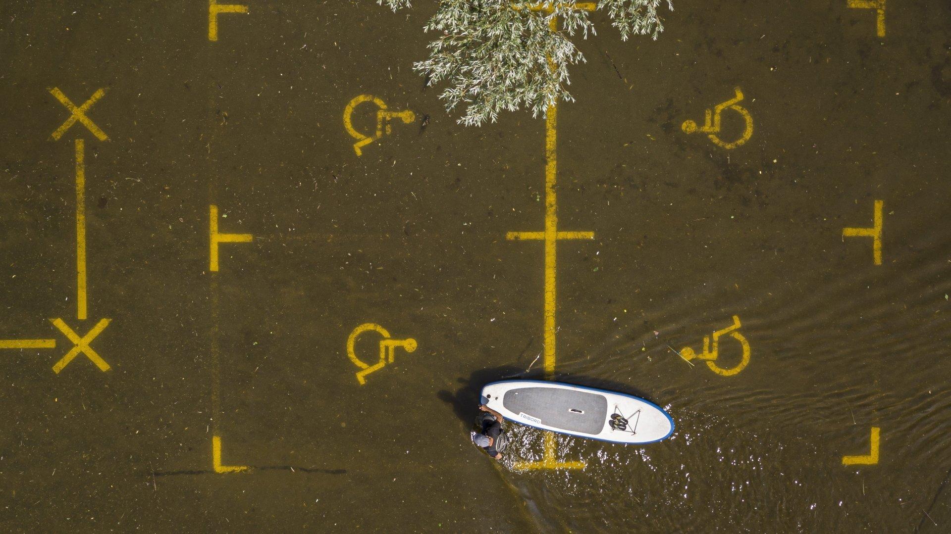 Un homme pousse son paddle à travers un parking inondé d'Estavayer-le-lac, ce lundi 19 juillet.