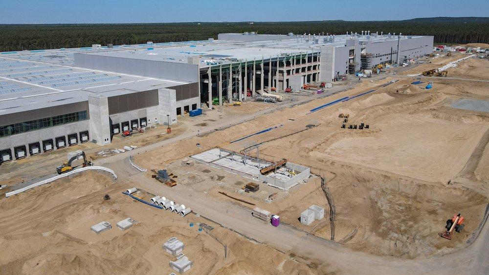 La nouvelle usine Tesla aux portes de Berlin se détache, immense quadrilatère blanc entouré de grues de chantier, sur le paysage fait de forêts sombres et de champs.