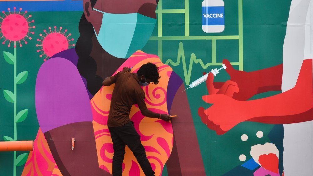 Un ouvrier met la touche finale à une immense fresque murale réalisée pour promouvoir la sensibilisation à la vaccination contre le coronavirus, Tambaram, Inde.