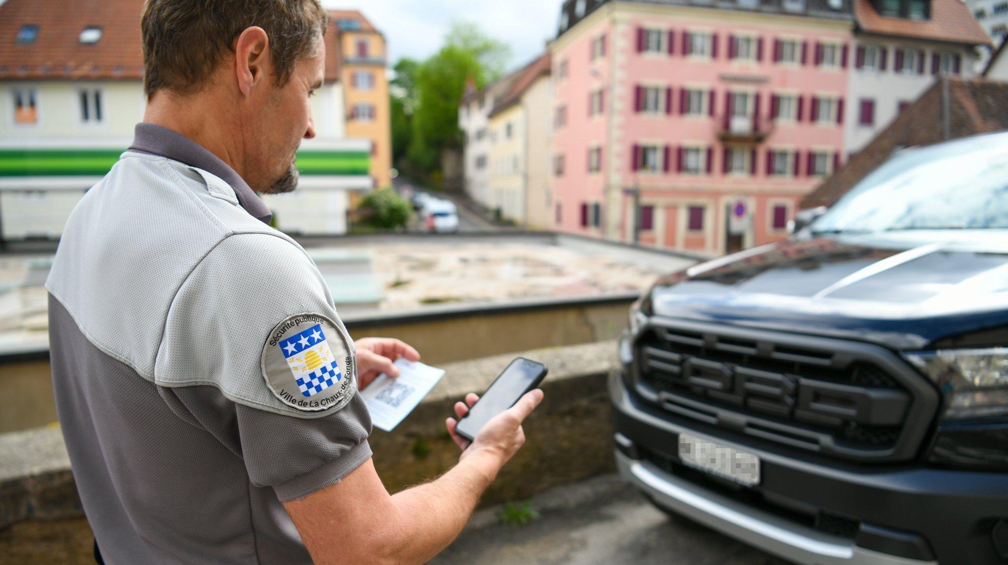 Un agent de la sécurité publique en train d'infliger une amende par QR code, à La Chaux-de-Fonds.