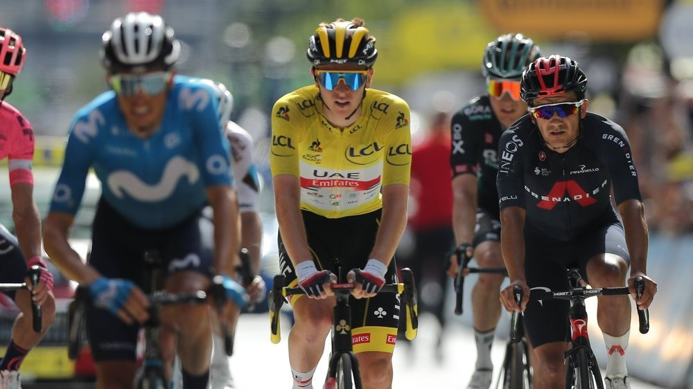 epa09337646 Slovenian rider Tadej Pogacar (C) of the UAE-Team Emirates wearing the overall leader's yellow jersey crosses the finish line of the 15th stage of the Tour de France 2021 over 191.3 km from Ceret, France to Andorra la Vella, Andorra, 11 July 2021.  EPA/CHRISTOPHE PETIT-TESSON