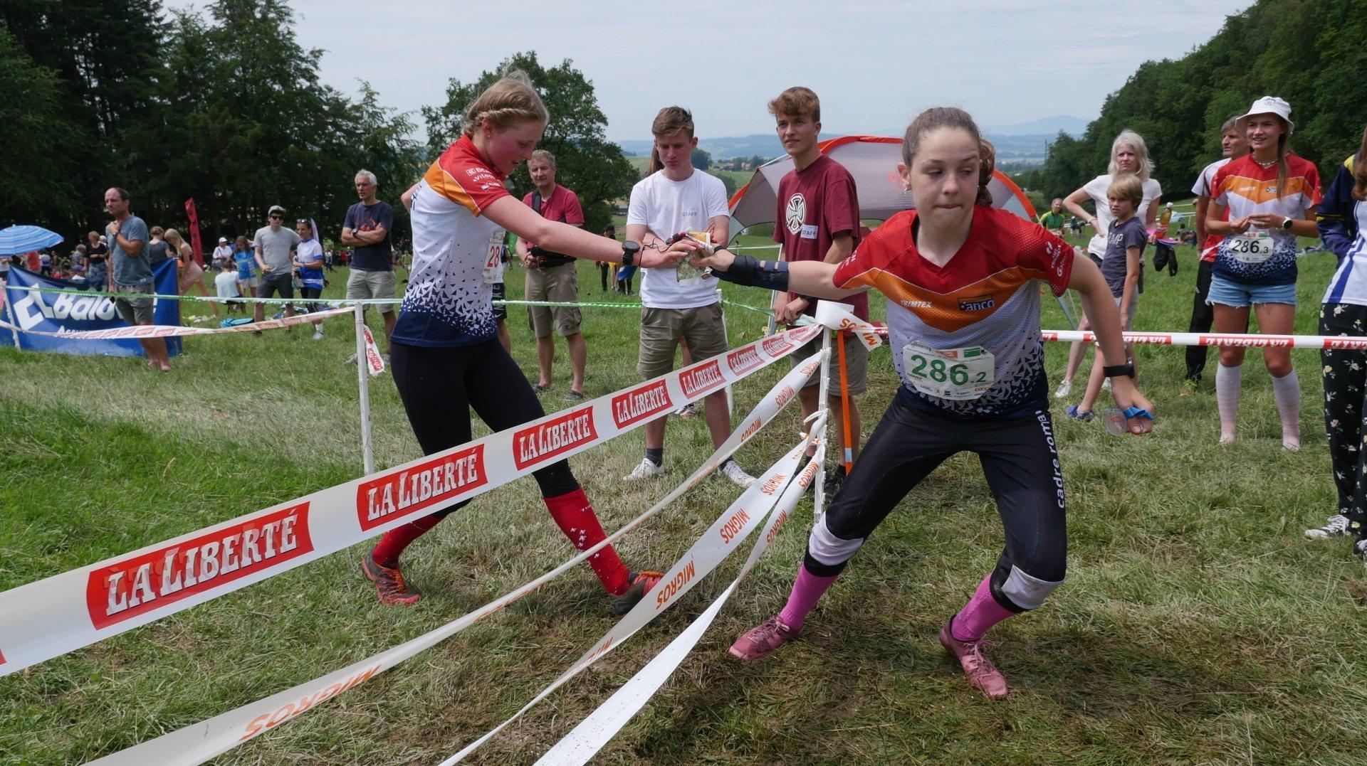 Inès Berger (à gauche) passe le témoin à Justine Hamel (à droite) lors du relais des championnats de Suisse d'orientation.