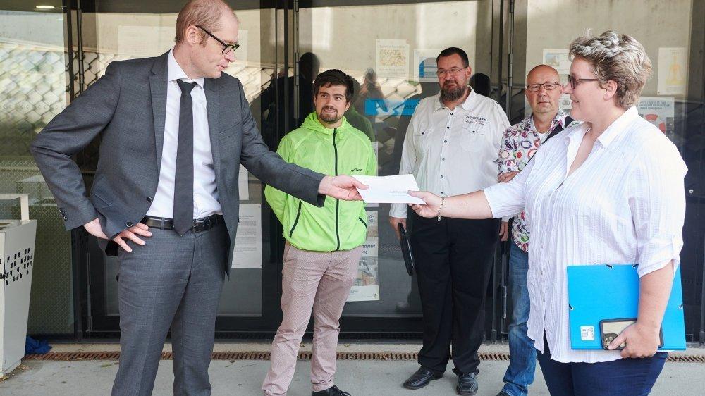 En tête de la délégation vert'libérale landeronaise, Jessica Muriset remet le texte du lancement de l'initiative au président de commune Frédéric Matthey.