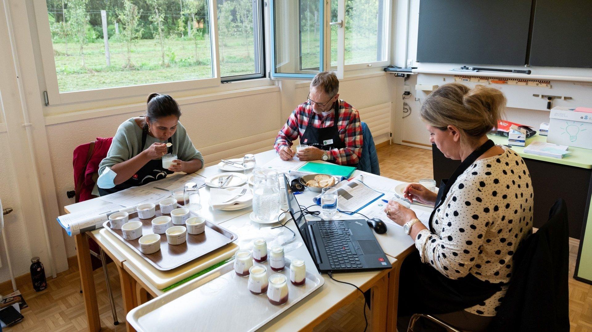 Un trio de juré.e.s en train de déguster des crèmes doubles à Courtemelon, dans le cadre du 9e Concours suisse des produits du terroir.