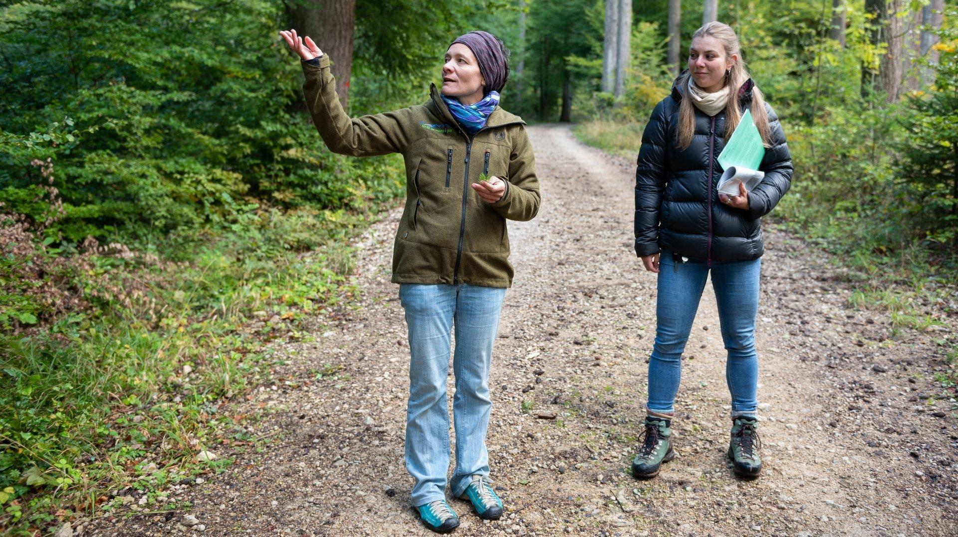 Gloria Locatelli et Laure Oberli (gauche à droite), respectivement présidente et membre de la Société neuchâteloise des forestiers (SFN), présentent le contour des sorties thématiques dans les hauteurs de Bevaix.