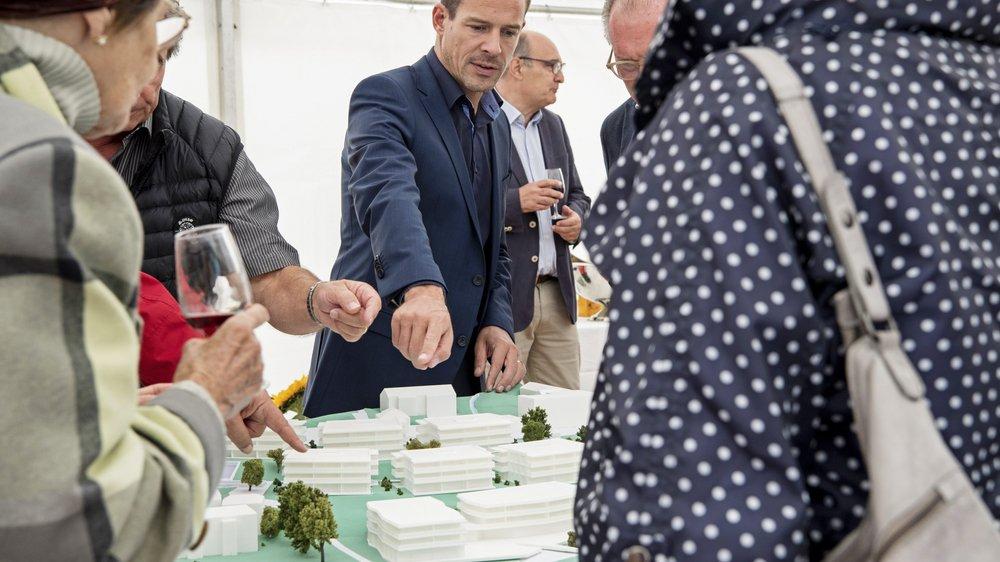 Robert Ischer (au centre), le directeur général du groupe Orllati, présente la maquette du complexe immobilier dont le chantier va s'ouvrir en octobre à Saint-Aubin.