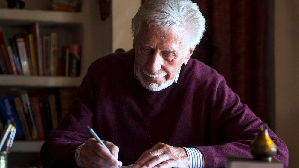 Willy Haag à sa table de travail, dans sa maison au centre du village de Bôle. Il ne se lasse pas de la beauté du décor du Littoral neuchâtelois,  où il vit depuis plus de 70 ans.