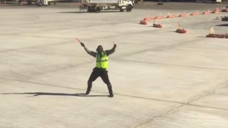 Quand un agent de piste d'aéroport guide un avion en dansant sur le tarmac