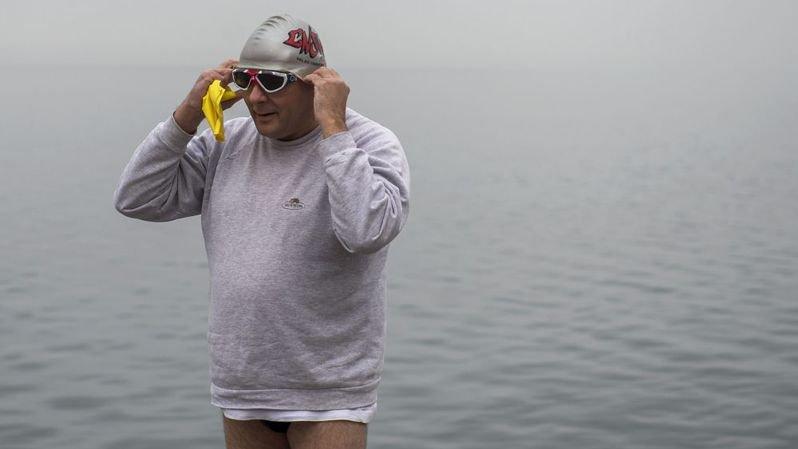 Un baigneur se prépare pour sa  baignade dans le lac, en hiver.