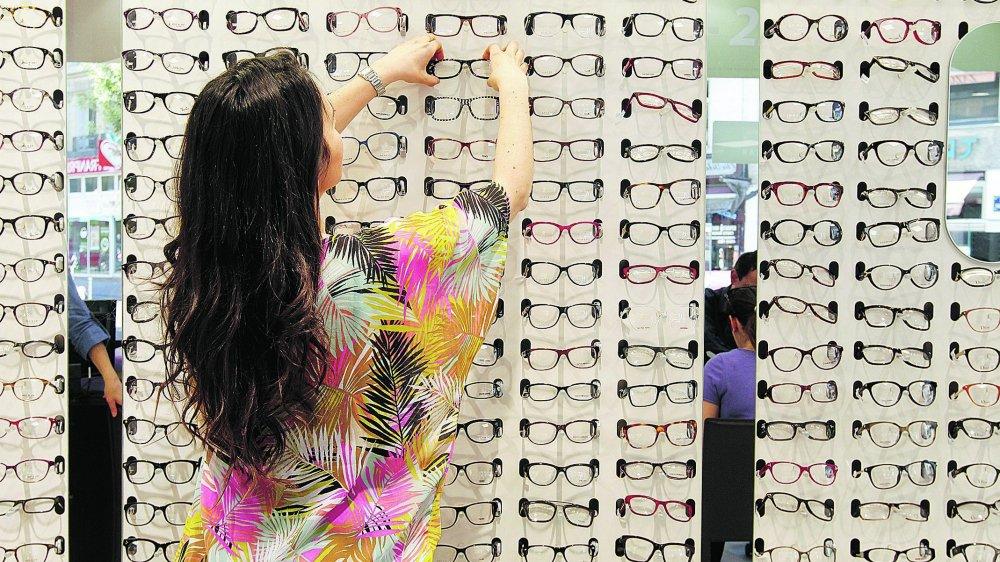 Ambiance dans un magasin Optic 2000 à Paris. Ici, une cliente essaye des montures de lunettes de vue.