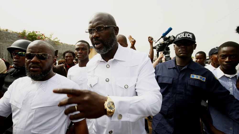 George Weah (au centre), hier à Monrovia, quelques minutes après avoir déposé son bulletin dans l'urne pour le 2e tour des élections présidentielles au Liberia. L'ex-star du football pourrait bien en sortir vainqueur.