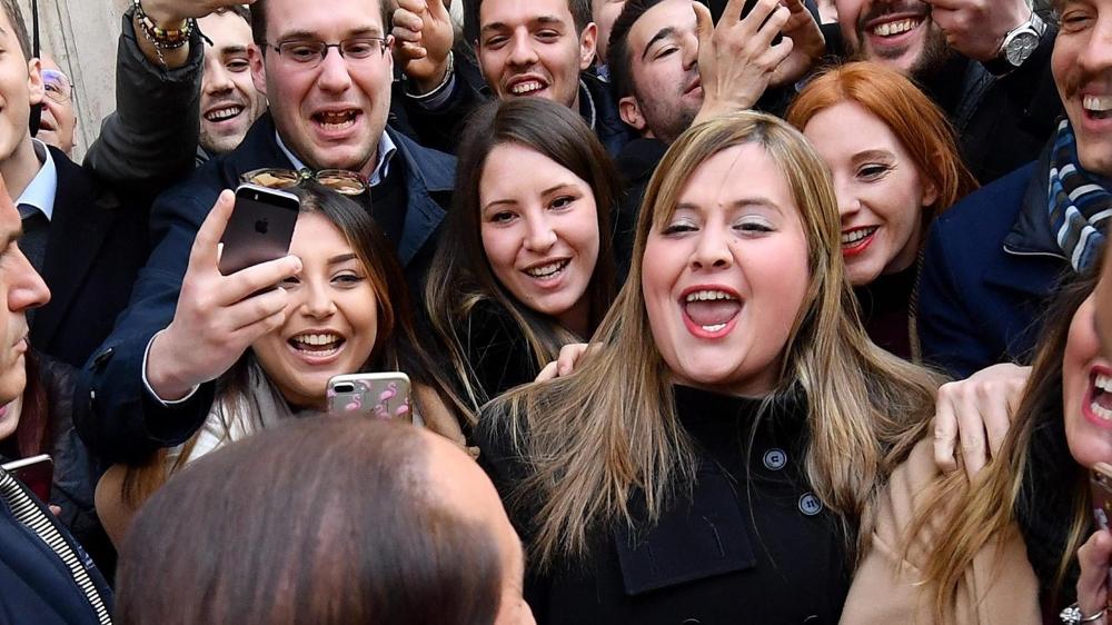 L'immigration est l'un des thèmes les plus débattus de la campagne des élections législatives en Italie.  Les partis – ici Silvio Berlusconi, de dos face à la foule – font de la surenchère sur le dos des réfugiés.