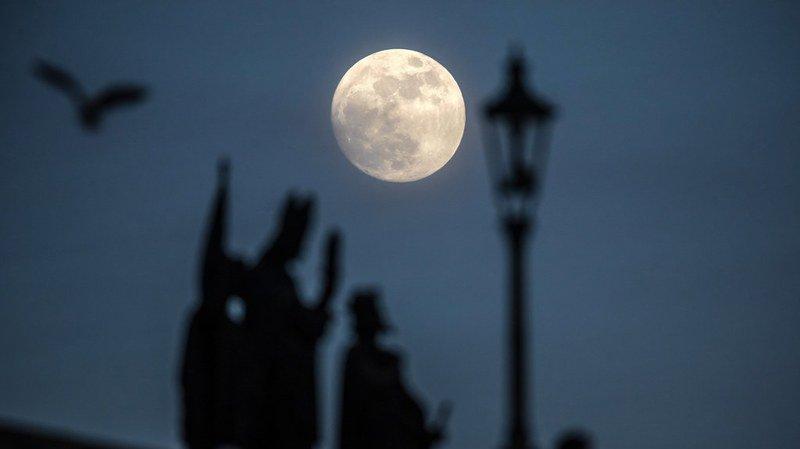 La Lune va attirer les regards plus que d'ordinaire, comme ici, au-dessus du Pont Charles de Prague, en République tchèque.