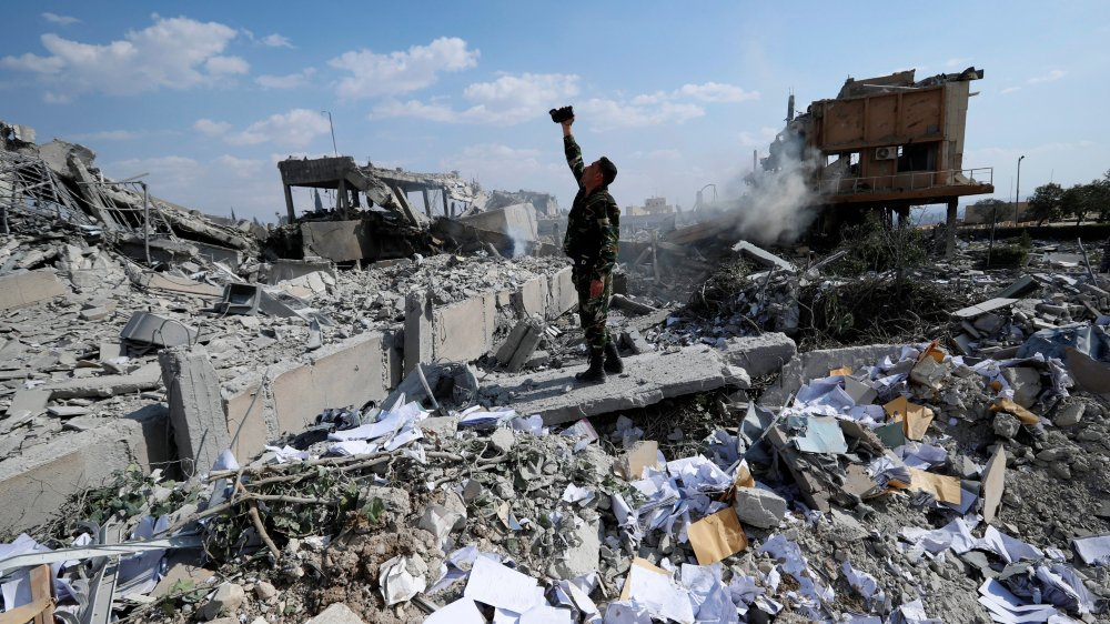 Un soldat syrien filme les ruines  d'un centre de recherche scientifique,  à Barzeh, près de Damas, détruit samedi dernier par les bombardements  occidentaux.