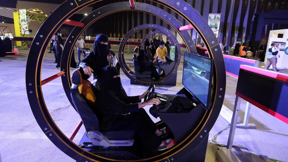 Des jeunes femmes s'initient aux rudiments de la conduite dans un simulateur, lors d'une foire, à Riyad.