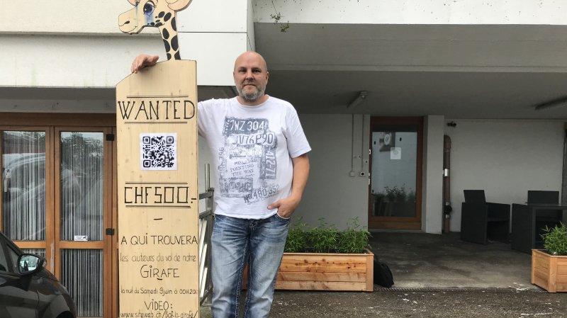 """Raphaël Vallat, patron de siteweb.ch pose à côté du panneau """"Wanted"""" qu'il a confectionné après le vol de la girafe mascotte de l'entreprise."""