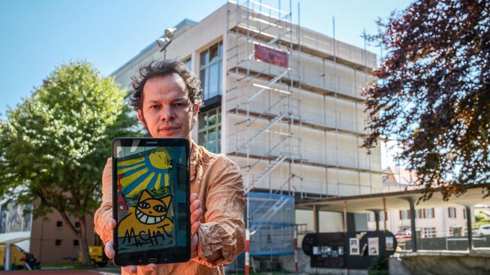 Monsieur Chat montre l'esquisse de la fresque qu'il réalise jusqu'à mercredi sur la façade du collège des Jeanneret derrière lui.