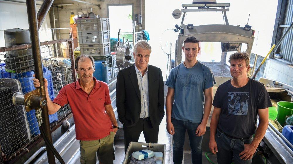 Heureux de la décision du Tribunal fédéral, trois de la trentaine de pêcheurs professionnels du lac de Neuchâtel entourant leur avocat Alexis Bolle.