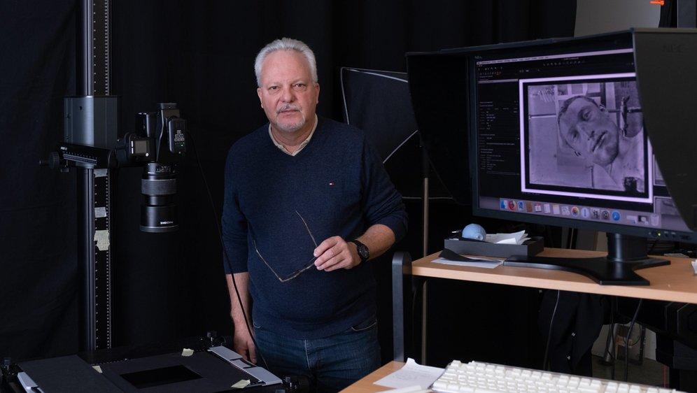 Christophe Brandt, le directeur de l'institut suisse pour la conservation de la photographie, devant l'un de clichés de scène de crime.