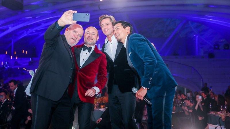 Le photographe Peter Lindbergh prend un selfie avec le patron de Breitling Georges Kern (en rouge) et les acteurs Brad Pitt et Daniel Wu.