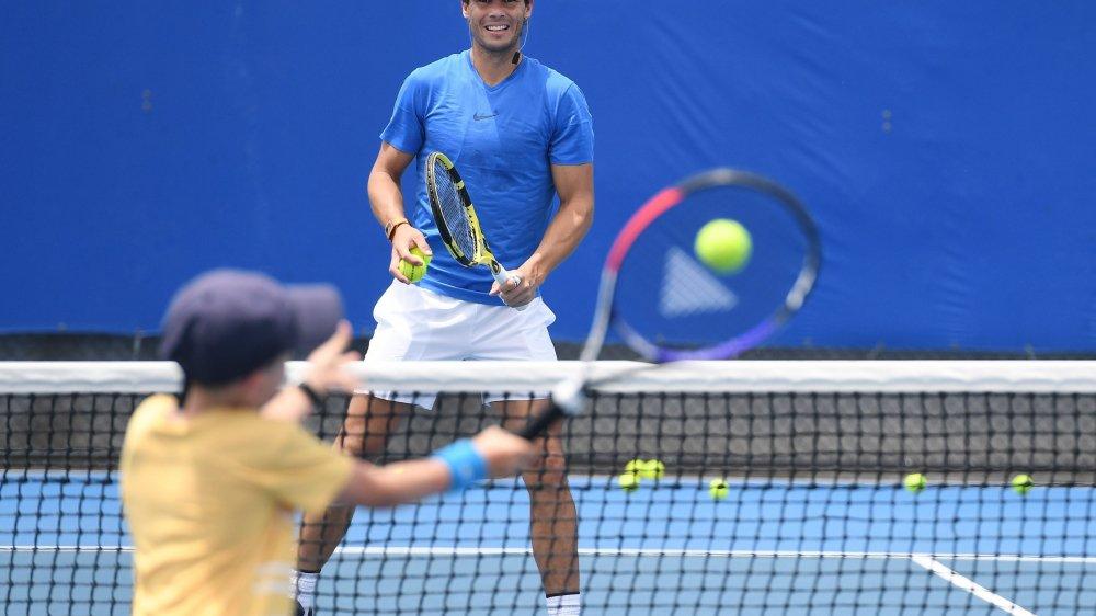Rafael Nadal, qui échange ici des balles avec un jeune joueur, aura-t-il encore le sourire après le tirage au sort?