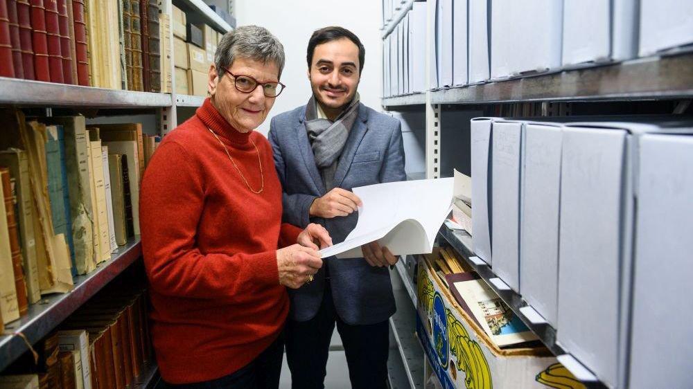 Loyse Renaud Hunziker, militante et ancienne élue, et Oğuzhan Can, secrétaire du Parti socialiste des Montagnes neuchâteloises, consultent les archives déposées à la bibliothèque de La Chaux-de-Fonds.