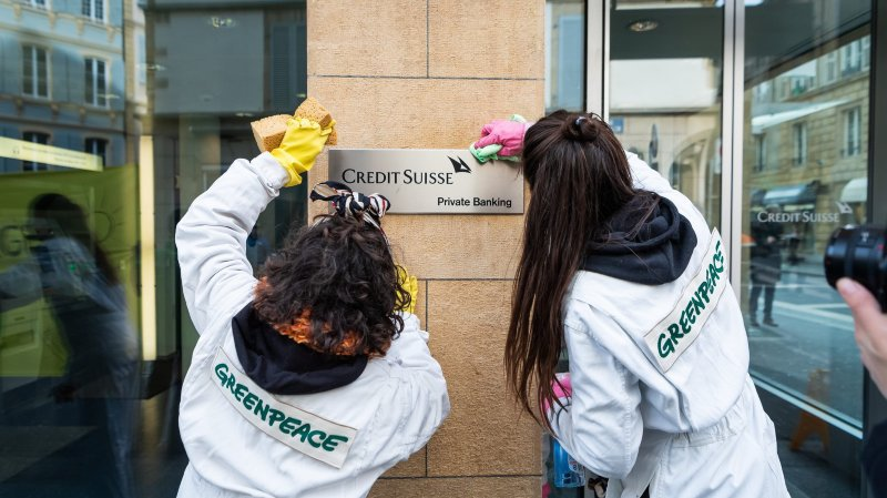 Des militants de Greenpeace font briller les carreaux de Credit Suisse à Neuchâtel