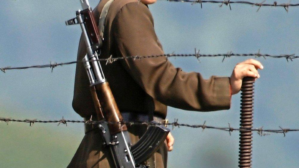 Femme soldat le long de la  barrière de sécurité d'un camp, dans le nord de la Corée du Nord. Le Comité pour les droits de l'homme y recense au moins  quatre camps de travail forcé  pour détenus politiques et une bonne vingtaine de camps de  rééducation par le travail.