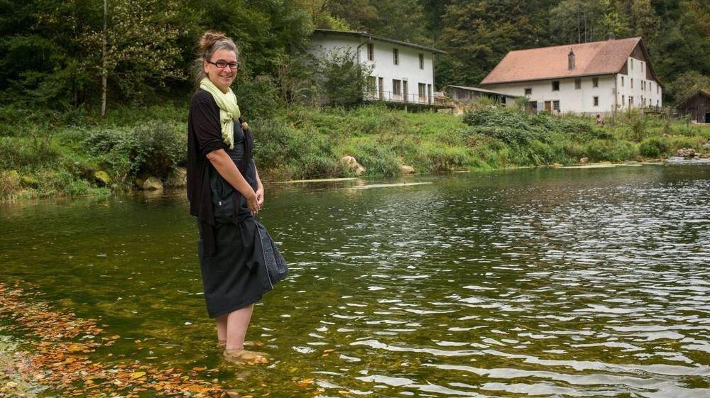 Phaedra Othman, pieds dans l'eau, avec le Moulin Jeannottat en arrière-plan.