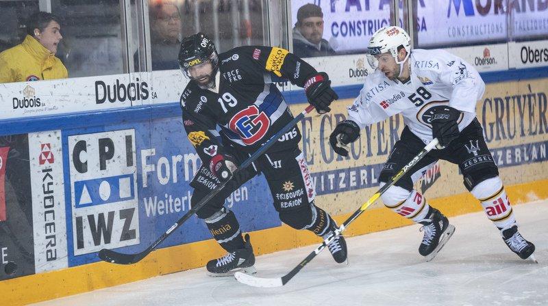 L'attaquant de Gottéron Laurent Meunier, à gauche, lutte pour le puck avec le defenseur de Lugano Romain Loeffel, à droite. Fribourg a perdu 3-1 contre Lugano.