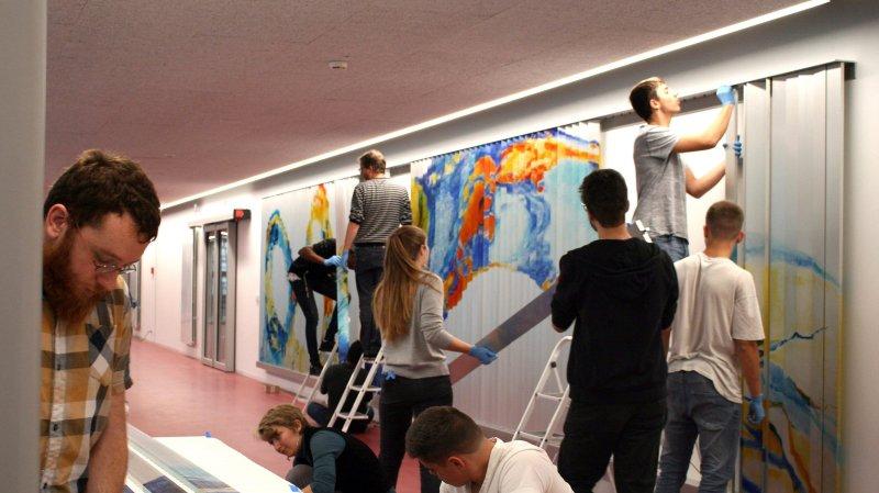 Les étudiants du CPLN en train de remonter la fresque mobile dans le hall de leur établissement.